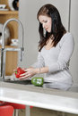 Woman rinsing peppers in a sink beautiful young preparing food her modern kitchen at home Stock Image