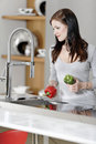 Woman rinsing peppers in a sink beautiful young preparing food her modern kitchen at home Royalty Free Stock Image
