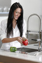 Woman rinsing peppers in a sink beautiful young preparing food her modern kitchen at home Stock Photo