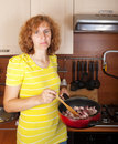 Woman roasting meat Stock Photos