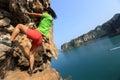 Woman rock climber climbing at seaside mountain rock Royalty Free Stock Photo