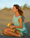 Woman with a rose on sand yellow in the dunes in the dress of mint color Stock Photo