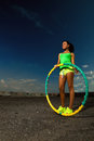 Woman rotates hula hoop against blue sky Royalty Free Stock Image