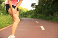 Woman runner holder her sports injured legs Royalty Free Stock Photo