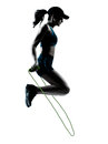 Woman runner jogger jumping rope one caucasian in silhouette studio isolated on white background Royalty Free Stock Image