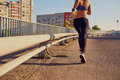 A woman runner jogs on a bridge in the city Royalty Free Stock Photo