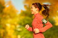 Woman runner running in fall autumn forest listening to music on smartphone using earphones female fitness girl jogging on path Royalty Free Stock Photos
