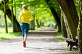 Woman runner running jogging in summer park and walking nature exercising bright forest outdoors Royalty Free Stock Images