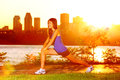 Woman runner stretching legs after running training in sunshine at sunset fit female jogger athlete training outside in montreal Royalty Free Stock Image