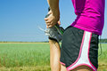 Woman runner stretching outdoors running on country road and exercising in summer nature female sport and fitness Royalty Free Stock Images
