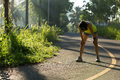 Woman runner take a break at morning tropical forest trail Royalty Free Stock Photo
