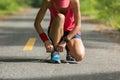 Woman runner tying shoelace before run on sunset beach Royalty Free Stock Photo