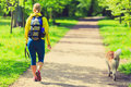 Woman runner walking with dog in summer park Royalty Free Stock Photo