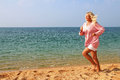 The woman running along the costline with closed eyes at beach against sea and sky Royalty Free Stock Photo
