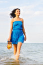 Woman running along edge of surf  slippers Stock Photography