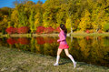 Woman running in autumn park, beautiful girl runner jogging outdoors Royalty Free Stock Photo