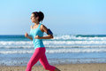 Woman running on beach with earphones fitness workout at the summer sporty girl wearing and sport armband for listening smartphone Stock Images