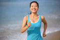 Woman running at beach young fit asian Royalty Free Stock Photo