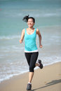 Woman running beach young fit asian seaside Royalty Free Stock Photography
