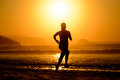 Woman running on beautiful sunset fitness at in the beach female athlete silhouette exercising sunrise nature scene Stock Photo