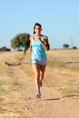 Woman running cross trail in country path side runner exercising and training for race fitness girl on summer rural landscape Stock Image