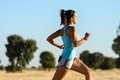 Woman running cross trail in country side runner sprinting and training for race fitness girl exercising on summer rural landscape Royalty Free Stock Images