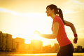 Woman running and exercising on beautiful golden summer sunset background on city beach female athlete fitness girl training copy Royalty Free Stock Photo