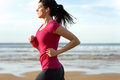 Woman running fast on beach at sunset brunette fitness girl runner exercising outdoors on sea background caucasian female athlete Stock Image