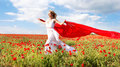 Woman running with red scarf in poppy field Royalty Free Stock Photography