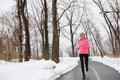 Woman running in snowy city park winter fitness jogging female athlete exercising outside cold weather on forest path wearing Royalty Free Stock Image