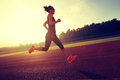 Woman running during sunny morning on stadium track Royalty Free Stock Photo