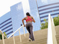 Woman running up stairs rear view tilt Stock Image
