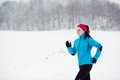 Woman running in winter athlete is during cold snow weather Royalty Free Stock Photo