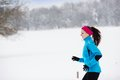 Woman running in winter athlete is during cold snow weather Royalty Free Stock Images