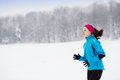 Woman running in winter athlete is during cold snow weather Stock Photo