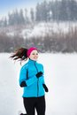 Woman running in winter athlete is during cold snow weather Stock Photos