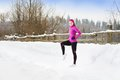 Woman running in winter athlete is during training outside cold snow weather Royalty Free Stock Photos