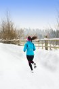 Woman running in winter athlete is during training outside cold snow weather Stock Image