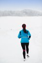 Woman running in winter athlete is during training outside cold snow weather Royalty Free Stock Images