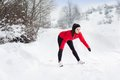Woman running in winter athlete is during training outside cold snow weather Stock Photography