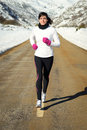 Woman running in winter on road girl exercising a mountain a snowy natural scenery Stock Image