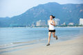 Woman running young fit asian seaside Stock Photos
