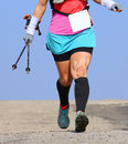 Woman runs with bandage at the knee and with Nordic walking pole Royalty Free Stock Photo