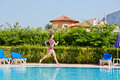 Woman runs at poolside around pool young Royalty Free Stock Photography