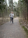 The woman runs on the track in the spring wood Stock Photos