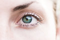 Woman s eye macro shot of a amazing green blue open with blurred face copy space natural and fresh look without makeup Royalty Free Stock Photo