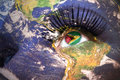 Woman`s  face with planet Earth texture and guyanese flag inside the eye. Royalty Free Stock Photo