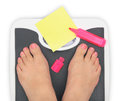 Woman s feet on bathroom scale and blank notepaper Royalty Free Stock Image