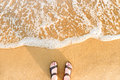 Woman`s feet in sandals on a beach sand Royalty Free Stock Photo