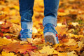 Woman's feet on a yellow autumn leafs background Stock Photos